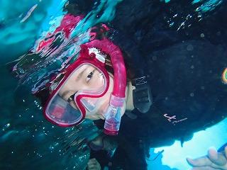 青く光る洞窟内でシュノーケリング